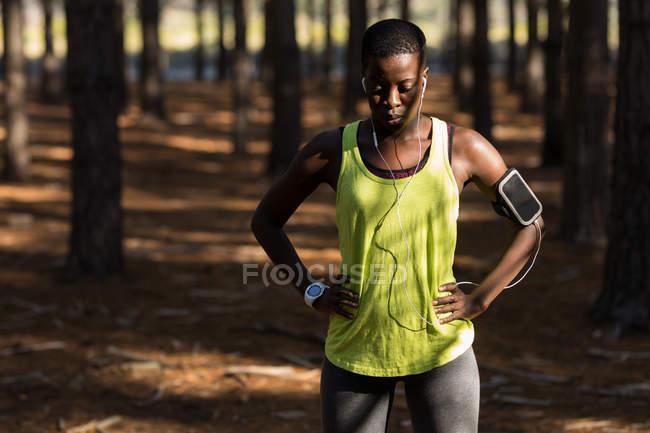Уставшая спортсменка отдыхает в лесу — стоковое фото
