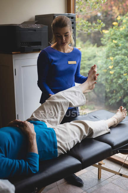 Physiotherapist assisting a senior woman with physiotherapy exercises at home — Stock Photo