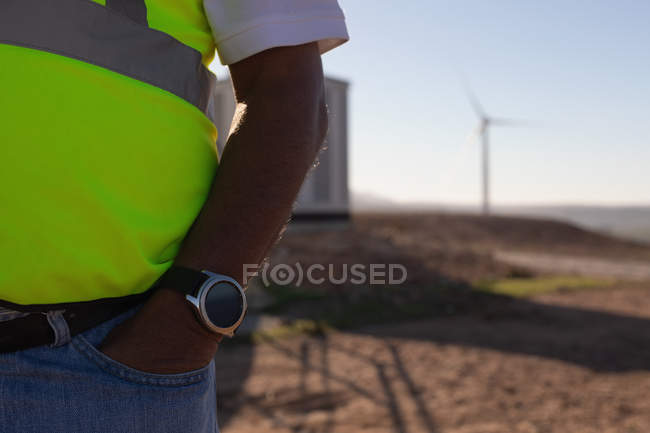 Engineer standing with hands in pocket at wind farm — Stock Photo