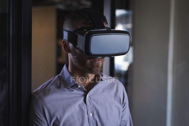 Empresario con auriculares de realidad virtual en la oficina - foto de stock