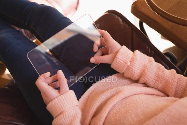 Девушка, использующая стеклянный цифровой планшет в гостиной на дому — стоковое фото
