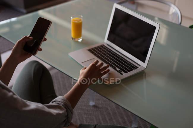 Mittelteil der Frau nutzt Handy und Laptop zu Hause — Stockfoto
