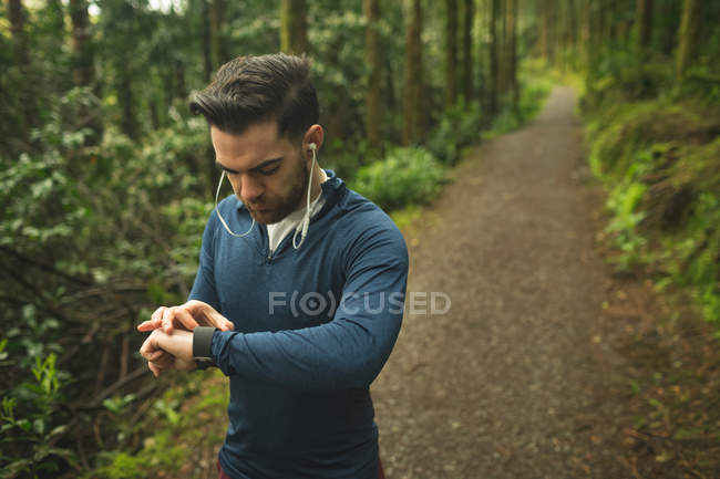 Красивий чоловік, перевіряючи час на smartwatch в лісі — стокове фото
