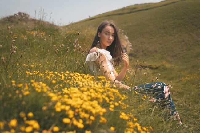 Mulher bonita sentada em um prado — Fotografia de Stock