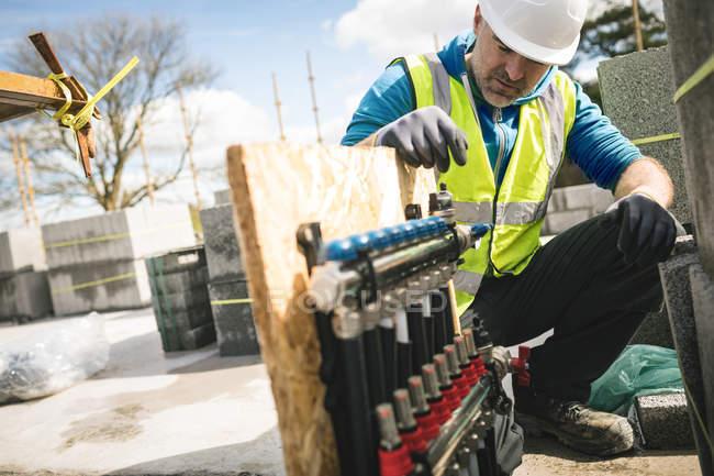 Bauarbeiter begutachtet Rohre vor Ort — Stockfoto