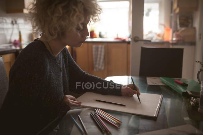 Mujer joven dibujando un boceto en casa - foto de stock