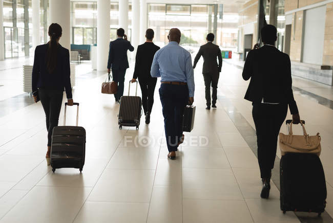 Group of business people walking with suitcase — Stock Photo