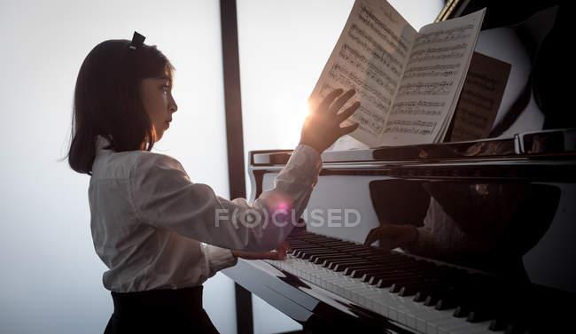 Entzückendes Schulmädchen spielt Klavier in der Musikschule — Stockfoto