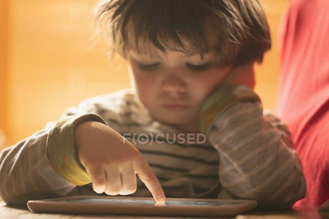 Крупный план мальчика с помощью цифровой вкладки дома — стоковое фото