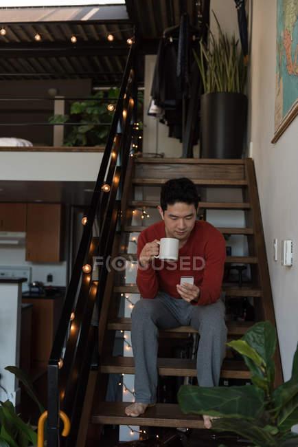 Человек, имея кофе при использовании мобильного телефона на лестнице дома — стоковое фото