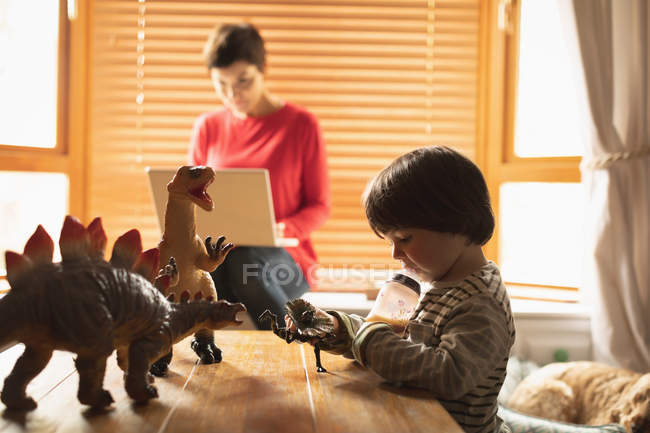 Niño juguetes mientras la madre utilizando el portátil en casa - foto de stock