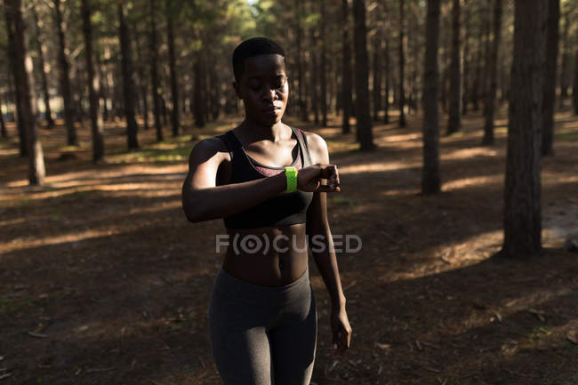 Female athlete checking her smartwatch in the forest — Stock Photo