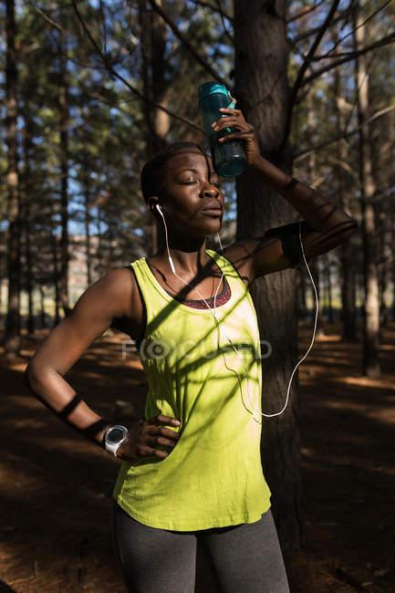 Спортсмен с бутылкой воды отдыхает в лесу — стоковое фото