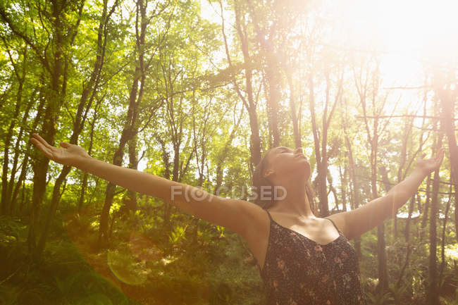 Woman with hands spread standing below bright sunlight in forest — Stock Photo