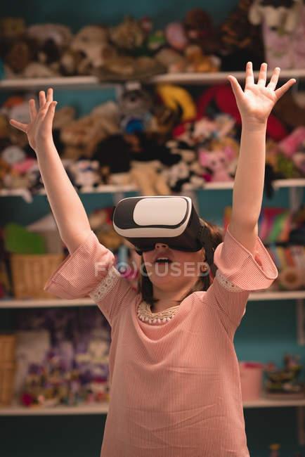 Chica usando auriculares de realidad virtual en la sala de estar en casa - foto de stock