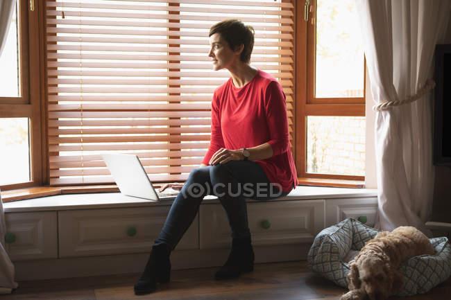 Женщина смотрит в окно во время использования ноутбука в гостиной на дому — стоковое фото