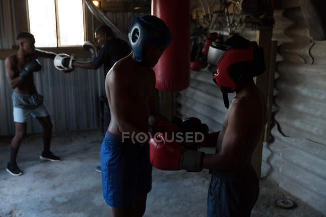 Treinador assistindo jovem boxeador masculino no estúdio de fitness — Fotografia de Stock