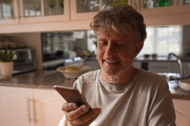 Senior man using mobile phone in the kitchen at home — Stock Photo