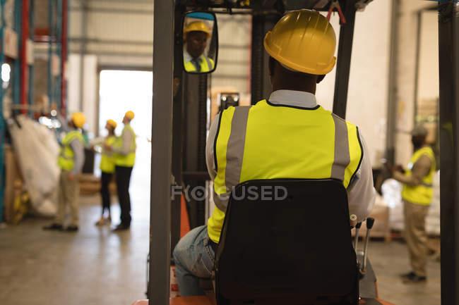 Carrello elevatore guida operaio maschio in magazzino — Foto stock
