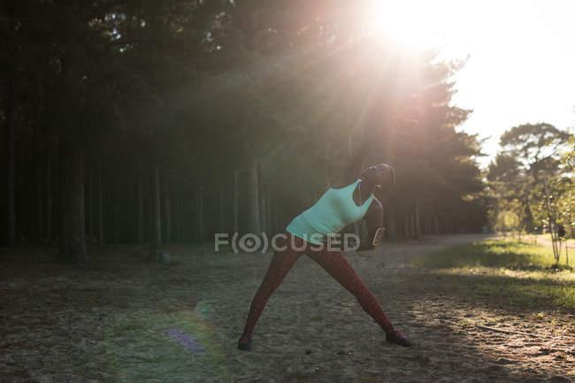 Спортсменка, выступающая утром в лесу на растяжке — стоковое фото
