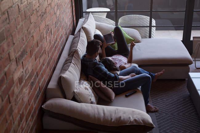 Пара с помощью цифрового планшета в гостиной на дому — стоковое фото