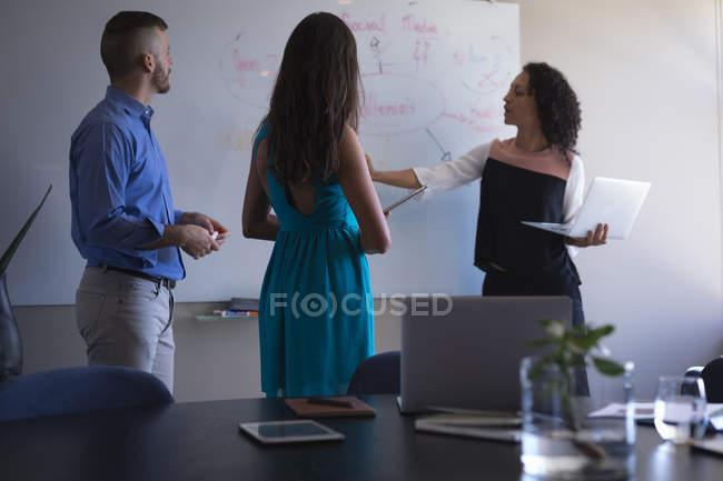 Dirigenti aziendali discutono sulla lavagna mentre utilizzano il computer portatile in ufficio — Foto stock