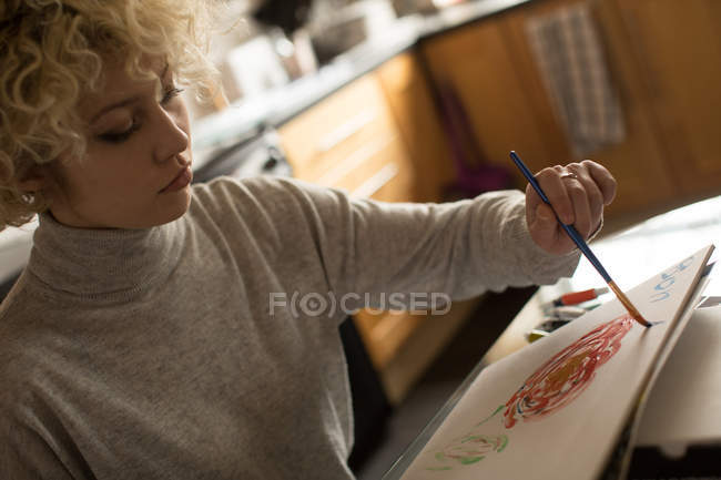 Young woman coloring a sketch at home — Stock Photo