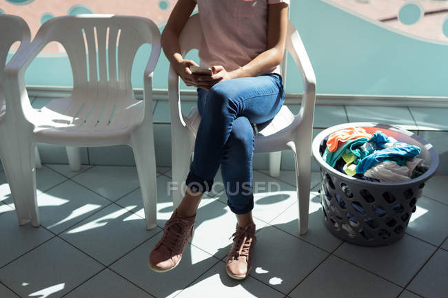 Low section of woman using mobile phone at laundromat — Stock Photo