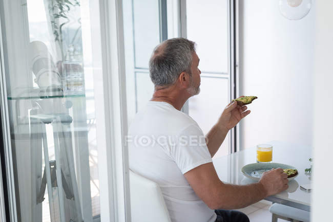 Mature man having breakfast at home — Stock Photo