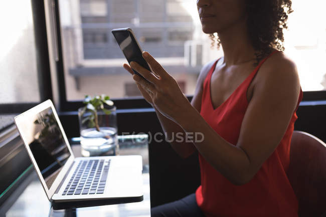Businesswoman sitting and using phone while working on laptop at office — Stock Photo