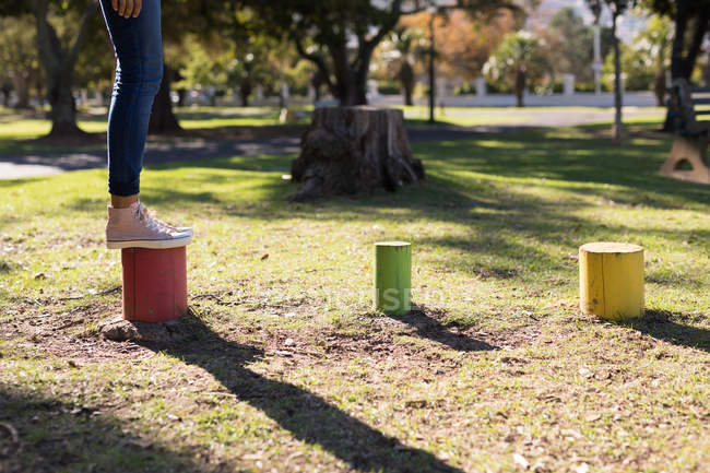 Woman stepping on colorful stumps in the park on a sunny day — Stock Photo