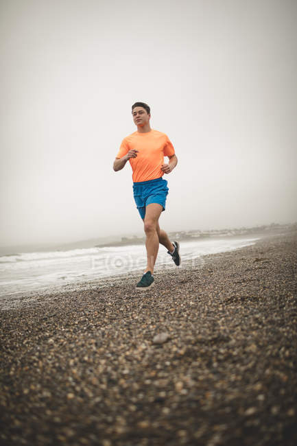 Young man jogging on shore at beach — Stock Photo