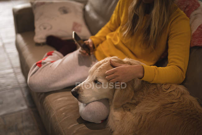 Girl with dog using mobile phone in living room at home — Stock Photo