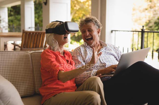 Älteres Paar mit Laptop und Vr Kopfhörer in Veranda zu Hause erleben — Stockfoto
