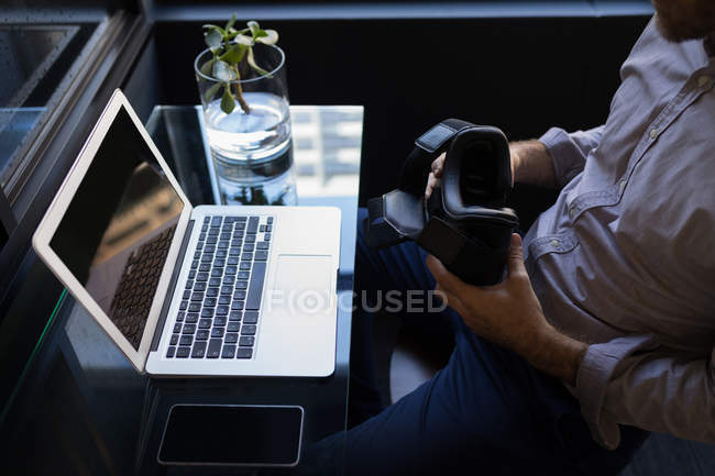 Businessman holding virtual reality headset while working on laptop at office — Stock Photo