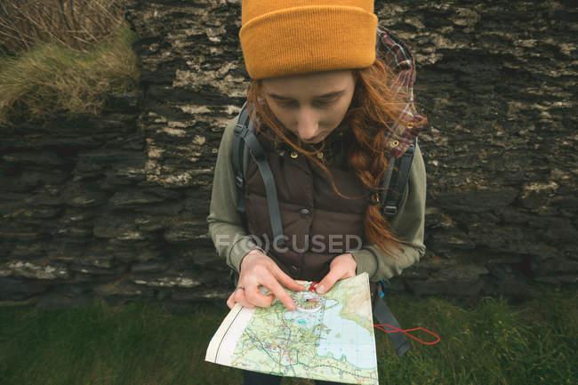 Nahaufnahme einer Wanderin, die sich an den Felsen lehnt und eine Landkarte liest — Stockfoto