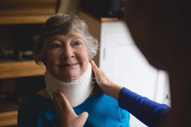 Крупный план физиотерапевта, устанавливающего шейный воротник на пожилую женщину — стоковое фото