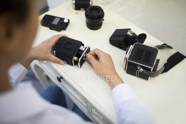 Female photographer removing reel from digital camera in photo studio — Stock Photo