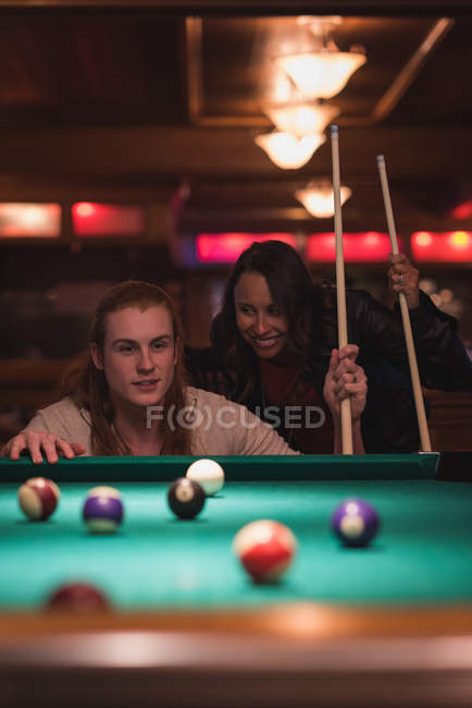 Couple playing snookers in the night club — Stock Photo