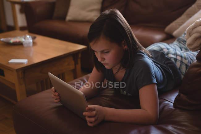 Menina usando tablet digital na sala de estar em casa — Fotografia de Stock