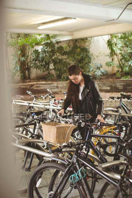 Belle femme parking son vélo — Photo de stock