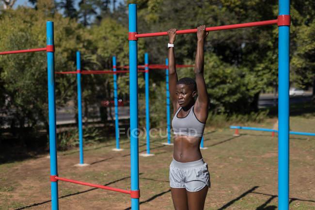 Решительная спортсменка, подтягивающая штангу — стоковое фото