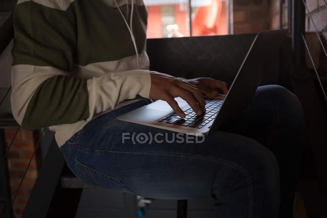 Seção média do homem usando laptop na escada em casa — Fotografia de Stock