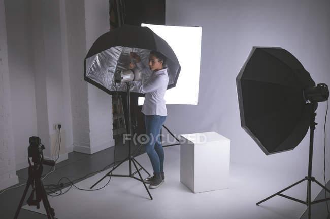 Fotografo femminile che regola le luci stroboscopiche — Foto stock