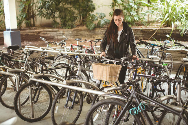 Belle femme parking son vélo — Photo de stock