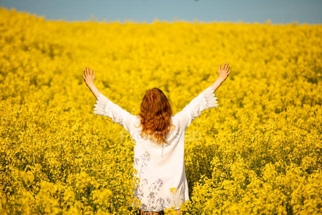 Rear view of woman with hand raised in the mustard field on a sunny day — Stock Photo