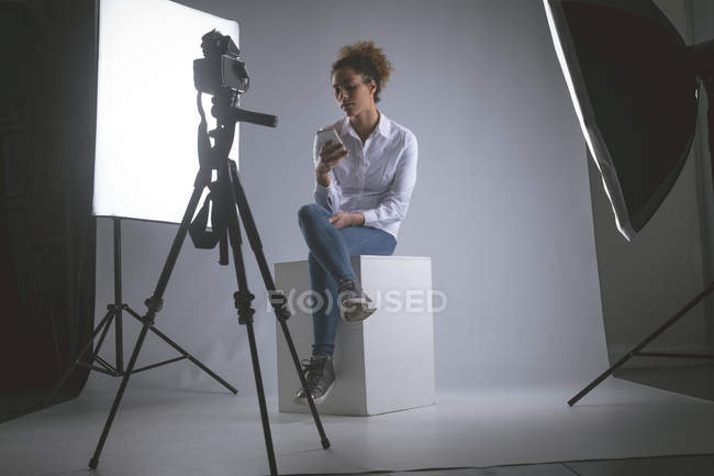 Female photographer using mobile phone in photo studio — Stock Photo