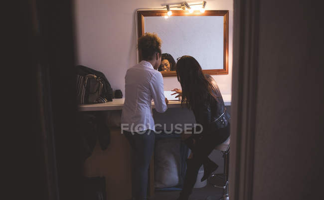 Female photographer and model using digital tablet in changing room — Stock Photo