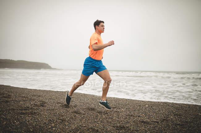Молода людина, біг на березі на пляжі — стокове фото