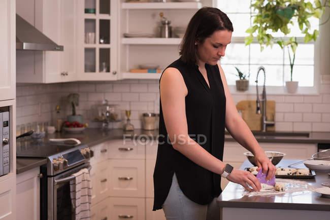 Femme préparant des galettes dans la cuisine à la maison — Photo de stock